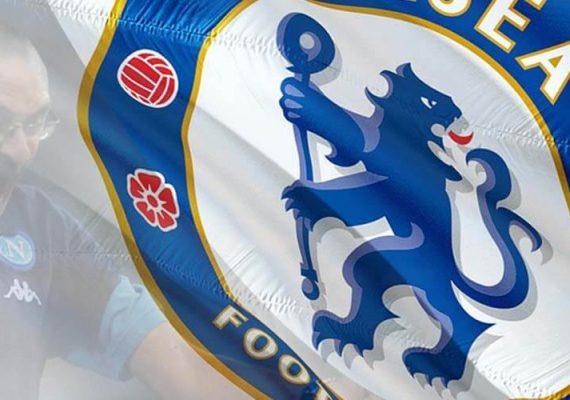 Chelsea's trainer Sarri rejoices next to the Chelsea's logo