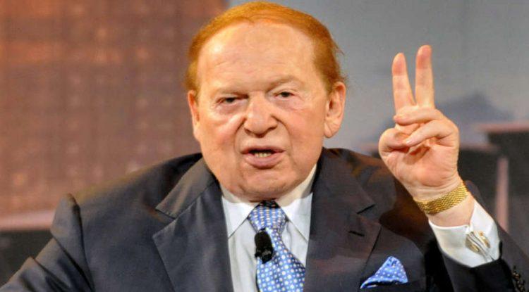Sheldon Adelson waves at the camera.