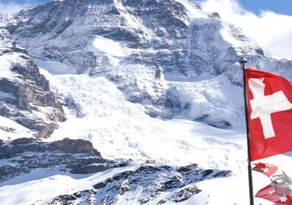 Switzerland's flag on a mountain top.