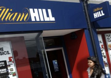 William Hill betting shop with a girl passing by.